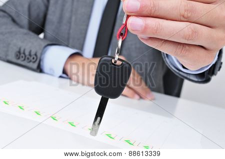 a young caucasian man in a grey suit sitting at his office desk gives a car key to the observer