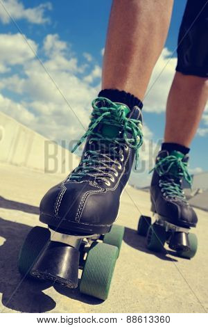 closeup of the feet of a young caucasian man roller skating with quad skates