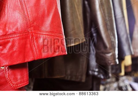 closeup of some used leather clothes, such as jackets and skirts, of different colors hanging on a rack in a flea market
