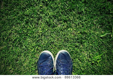 closeup of the feet of a man wearing blue shoes stepping on the grass, with a slight vignette added