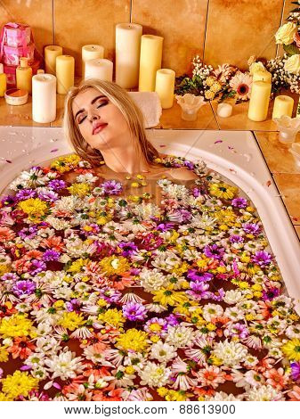 Woman relaxing at water spa. Aqueous surface covers a lot of colored flower heads.