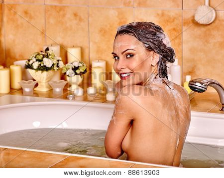 Woman relaxing at water in bubble bath. Girl looking to side. Flower background.