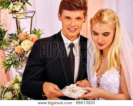 Happy wedding couple holding pillow with wedding ring. Flower on background.