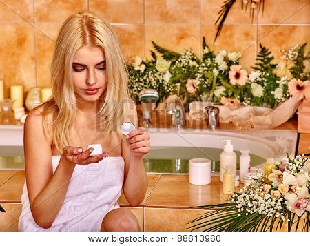 Woman applying moisturizer at bathroom. Cosmetic box.