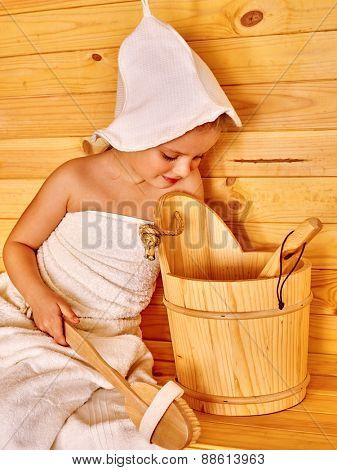 Happy child relaxing at sauna. Wooden bucket