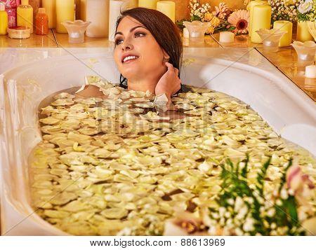 Woman relaxing at water spa. White rose petal.