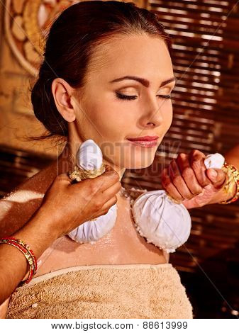 Woman having ayurvedic massage with pouch of rice. Brown background.