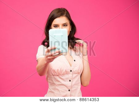 Young woman holding mirror and looking on it over pink background