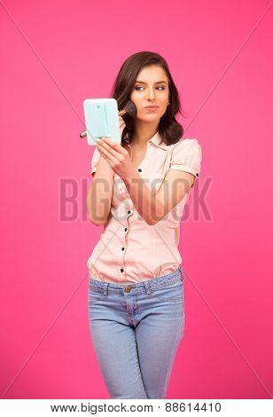 Attractive young woman making makeup over pink background. Holding mirror. Wearing in shirt and jeans