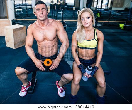 Muscular man and fit woman resting on the bench at gym and looking at camera