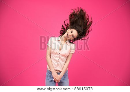 Funny happy woman posing over pink background