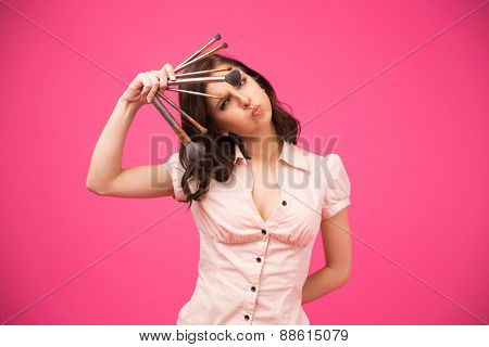 Funny young woman holding brushes over pink background. Looking at camera