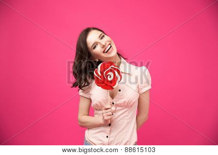 Laughing young woman holding lollipop over pink background and looking at camera