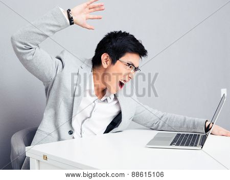 Angry young businessman in glasses sitting at the table with laptop over gray background