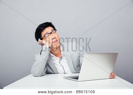 Young asian businessman sleepig at the table with laptop over gray background
