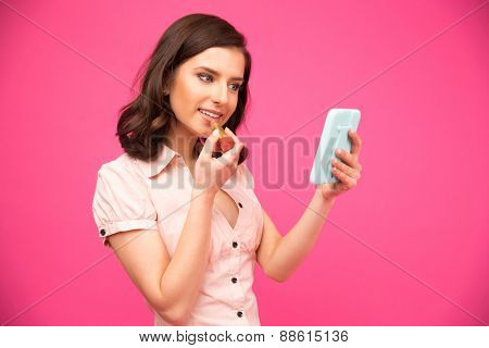 Happy woman holding mirror and putting lipstick on lips over pink background