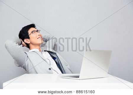 Happy young businessman resting at the table with laptop over gray background