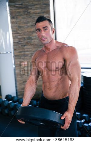 Handsome muscular man holding weight and looking at camera in gym
