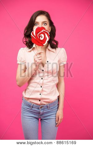 Young woman covering her face with lollipop over pink background. Wearing in shirt and jeans. Looking at camera