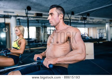Muscular man and sporty woman workout on training simulator in crossfit gym