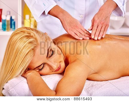 Blond woman getting massage in health resort. Eyes closed.