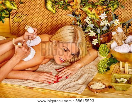 Blond woman getting massage in tropical spa. Bamboo background.