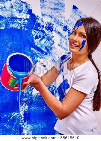 Happy woman paint wall at home. Pouring liquid.