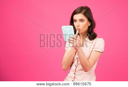 Young woman holding mirror and putting lipstick on lips over pink background