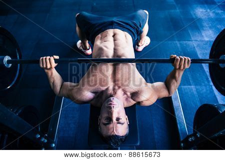Muscular man workout with barbell on bench at gym