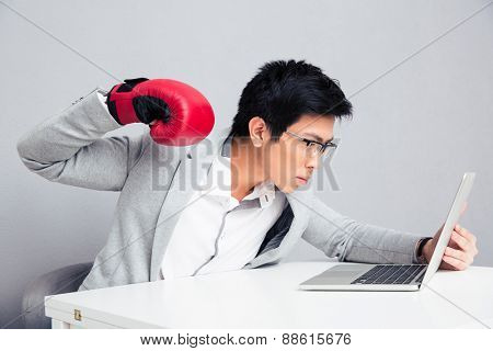 Young businessman in boxing gloves and glasses sitting at the table and reading to hit laptop over gray background