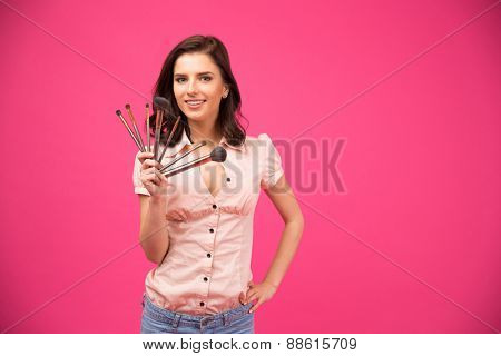 Smiling young woman holding brushes for makeup over pink background