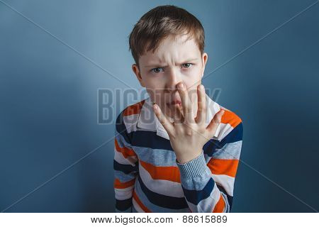 European-looking boy  of ten years licks his finger on a gray ba