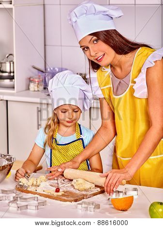 Mother and granddaughter baking cookies. Hat on head.