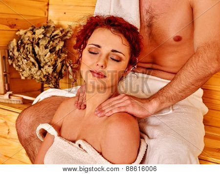 Couple man and woman    relaxing at sauna. Man does girl massage.