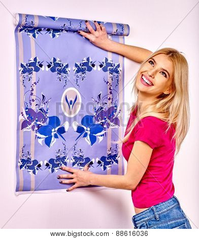 Happy woman glues wallpaper at home.