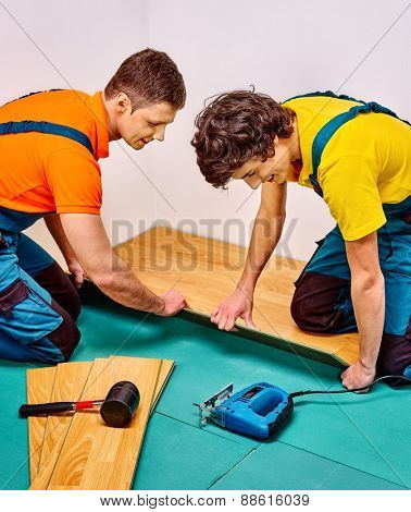 Happy men laying parquet at home. Two people.