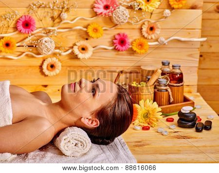 Woman getting stone therapy massage in wooden gerbal spa.