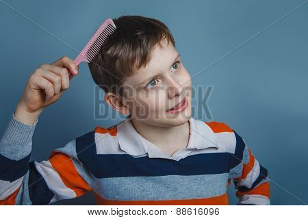 European-looking boy of ten years combing her hair on a gray bac