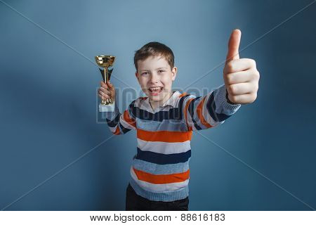 European-looking boy of ten years holding a cup award thumbs up