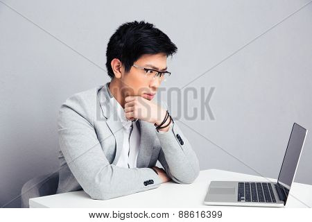Pensive businessman sitting at the table with laptop over gray background and looking on laptop