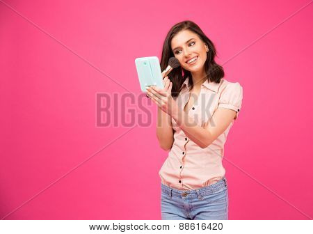 Happy woman holding mirror and making makeup over pink background