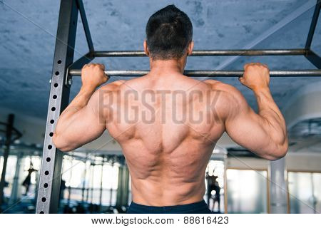 Back view portrait of a handsome muscular man pulling up at gym