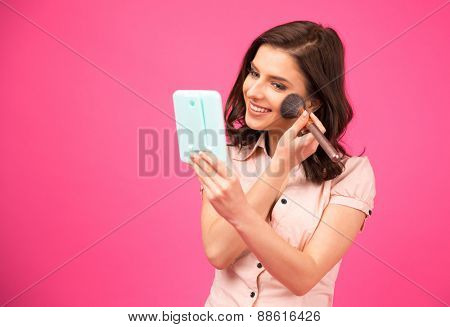 Beautiful woman making makeup over pink background
