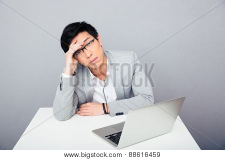 Asian businessman sitting at the table with laptop and looking at camera over gray background