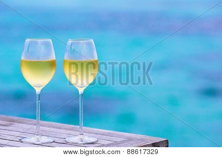 Two glasses of tasty white wine background the sea