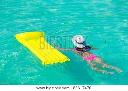 Woman relaxing on inflatable air mattress at turquoise water