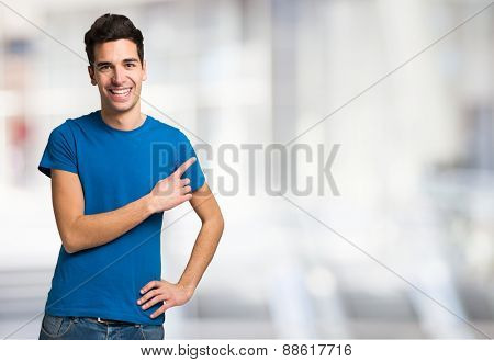 Young smiling man pointing his finger to the copyspace