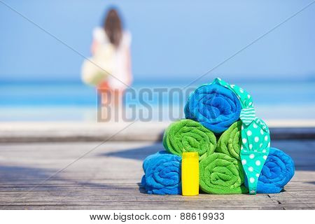Beach and summer accessories concept - colorful towels, swimsuit and sunsblock