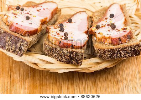 Three Sandwiches With Bacon And Peppers In Wicker Basket