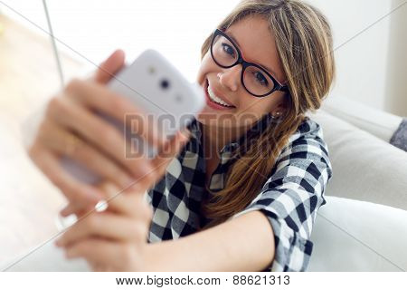 Beautiful Young Woman Using Her Mobile Phone At Home.